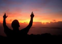 Man with his arms raised in praise at sunset