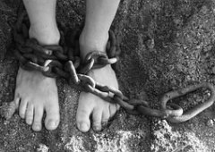 Chains wrapped around a pair of feet, depictng slavery