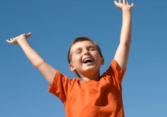 Young boy praising God with outstretched arms