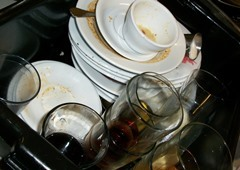 A pile of dirty dishes, cups, glasses