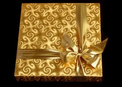 A present in a golden gift box with a golden bow