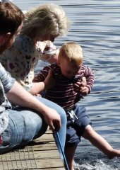 Grandmother holding a child so he looks like he's walking on the water