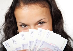 A girl holding money in front of her face with a glint in her eyes