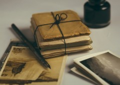 old letters, a pen, an ink pot and old photographs