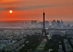 Eiffel Tower with sun in background and a view of Paris
