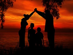 Parents hold their arms over their children with an orange/red sky in the background