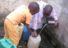 Two boys in Africa collecting pipe water into plastic containers