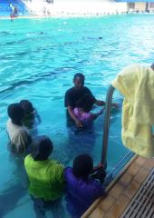 Believers being baptised at a swimming pool on Nairobi